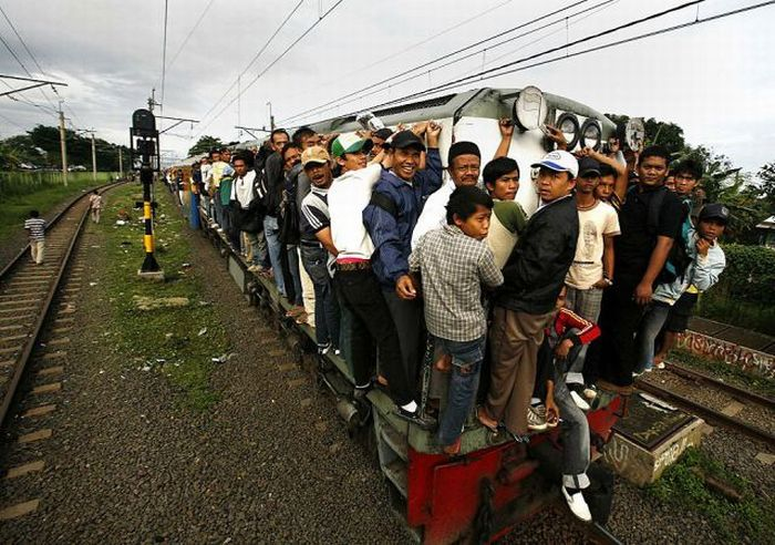 Men hang on to an overcrowded commuter train at Sudimara train station as they travel to Jakarta