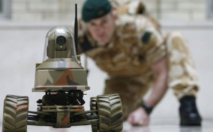 A Royal Marine poses with the Unmanned Vehicle Robot, Testudo, at the launch of the Defence Technology Plan in London